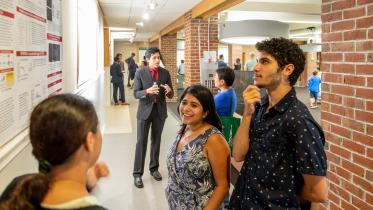 Students talk during a poster session.