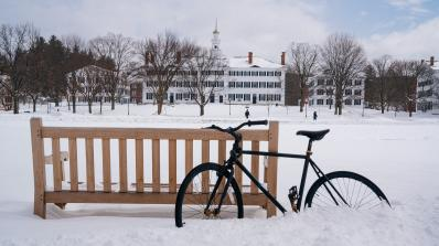 A bike leans against a bench in winter.