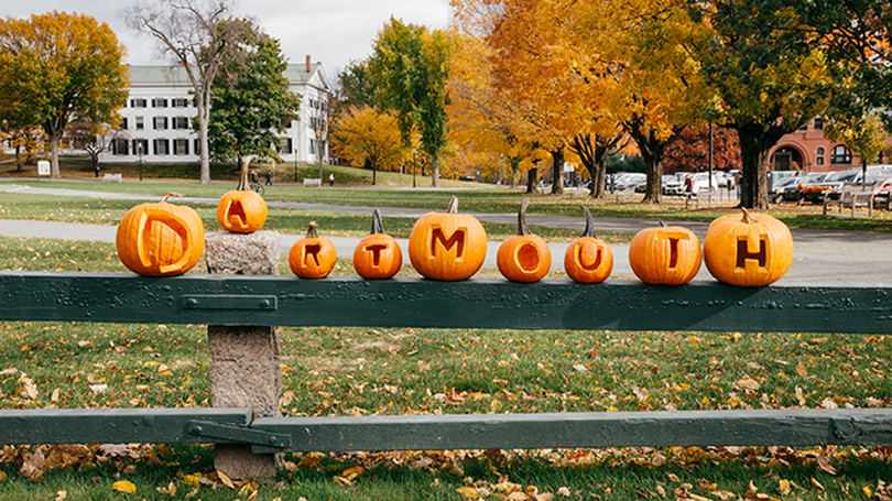 "Carved pumpkins spelling ""Dartmouth"" sit on a fence."