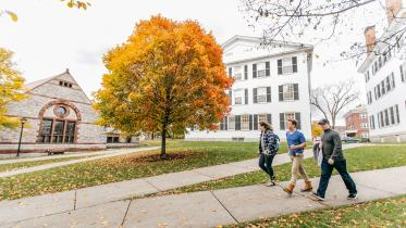 Students walk in the fall foliage.