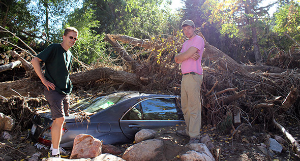 Professor Carl Renshaw, left, and graduate student Jimmy Voorhis survey the damage in the wake of flooding in Boulder, Colo.