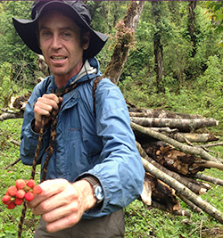 Brian Young carrying wood and holding berries.