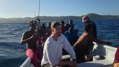 Tyler Pavlowich  sitting in a boat with a group of fishermen
