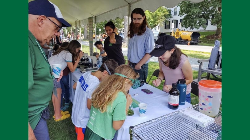 families and students engage in science activities on the green