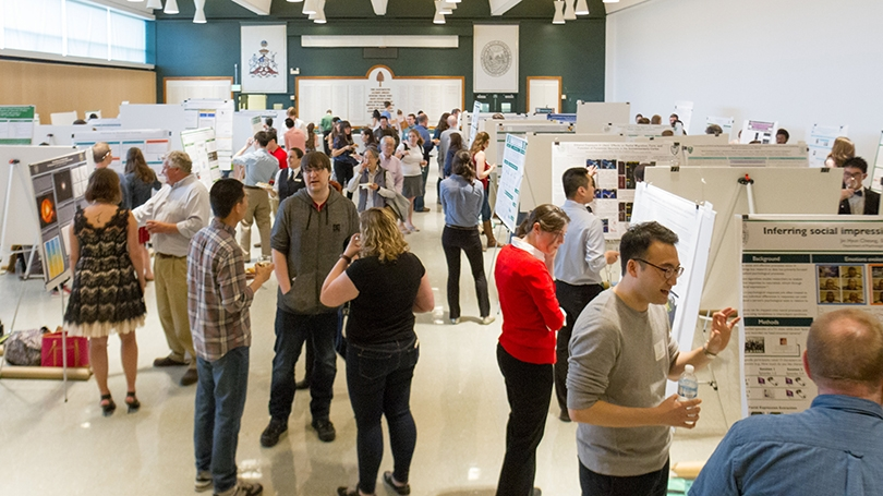 a crowd of people and displays of graduate research posters inside Alumni Hall at Dartmouth