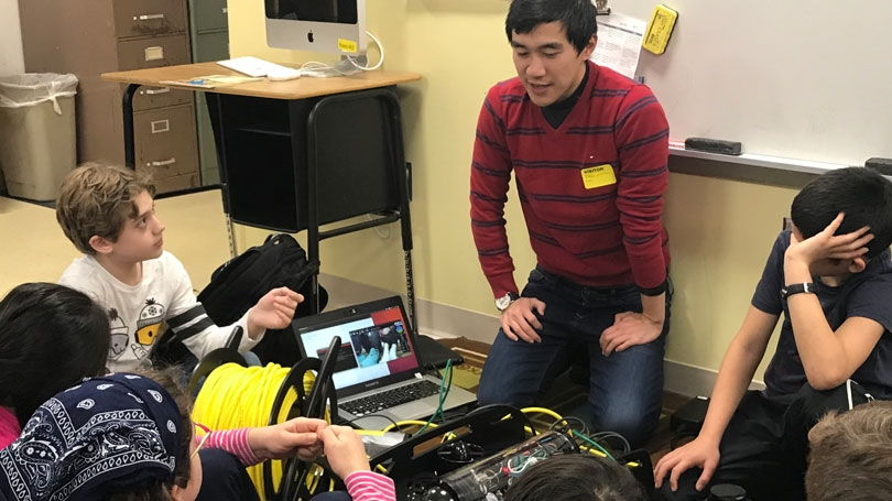 Professor Alberto Quattrini Li demonstrates an underwater robot and a small ground robot